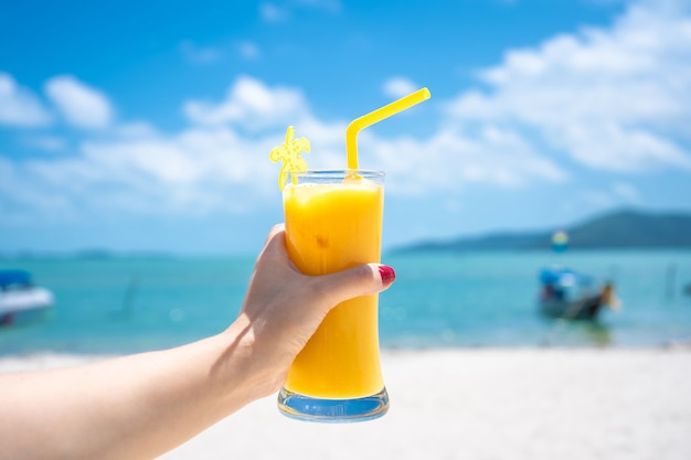 Widok z pierwszej osoby. dziewczyna trzyma szklaną filiżankę zimnego mango świeżego na tle piaszczystej tropikalnej plaży. biały piasek i łódź. bajkowe wakacje w tajlandii
