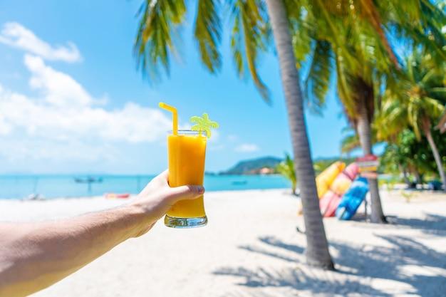 Widok z pierwszej osoby. dziewczyna trzyma szklaną filiżankę zimnego mango świeżego na tle piaszczystej tropikalnej plaży. biały piasek i palmy. bajkowe wakacje