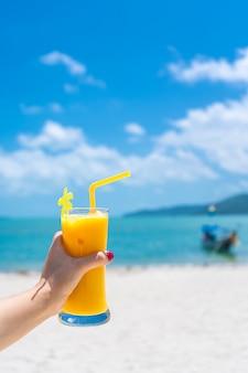 Widok z pierwszej osoby. dziewczyna trzyma szklany kubek zimnego mango świeżego na ścianie piaszczystej tropikalnej plaży. biały piasek i łódź. bajkowe wakacje w tajlandii