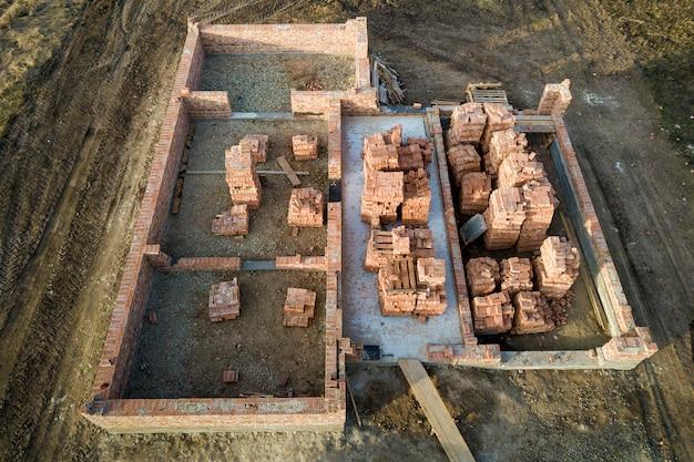 Widok z placu budowy. rowy wykopane w ziemi i wypełnione cementem jako fundament przyszłego domu, ceglana podłoga piwnicy i stosy cegieł do budowy.
