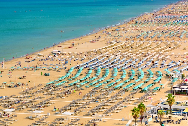 Widok z plaży rimini z ludźmi i błękitne wody. koncepcja letnich wakacji.