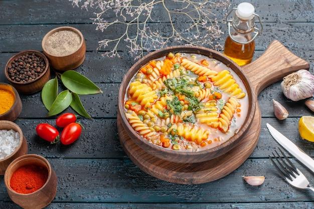 Widok z pół góry pyszna zupa z makaronu ze spiralnego włoskiego makaronu z przyprawami na ciemnoniebieskim biurku zupa z makaronu kolor danie obiad kuchnia