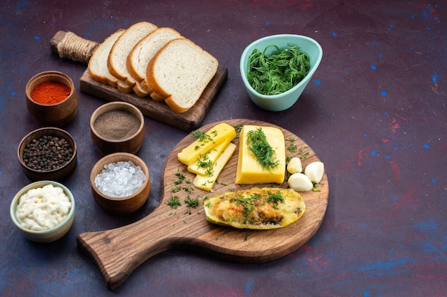 Widok z połowy góry gotował smaczne kabaczki z przyprawami, zielonym serem i bochenkami chleba na ciemnofioletowym biurku.