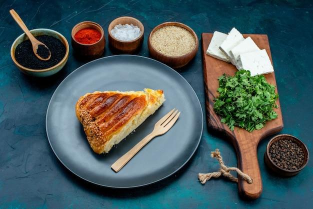 Widok z połowy góry pokrojone pyszne ciasto ze świeżymi zieleniami i białym serem na ciemnoniebieskim cieście backgruond pieczenie ciasta ser jedzenie posiłek