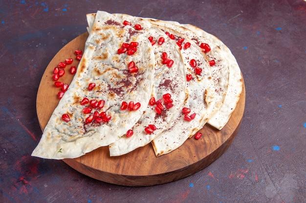 Widok z połowy góry pyszne pity mięsne qutabs ze świeżymi czerwonymi granatami na ciemnofioletowej powierzchni mączka mięsna z ciasta pita