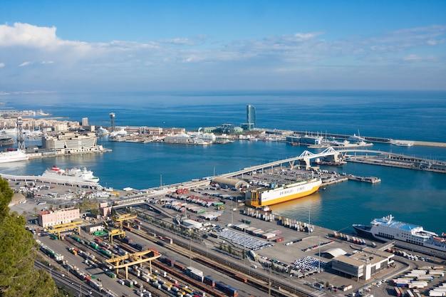 Widok z portu przemysłowego zamku montjuic w barcelonie zadokowany ze statkami, dźwigami i kontenerami
