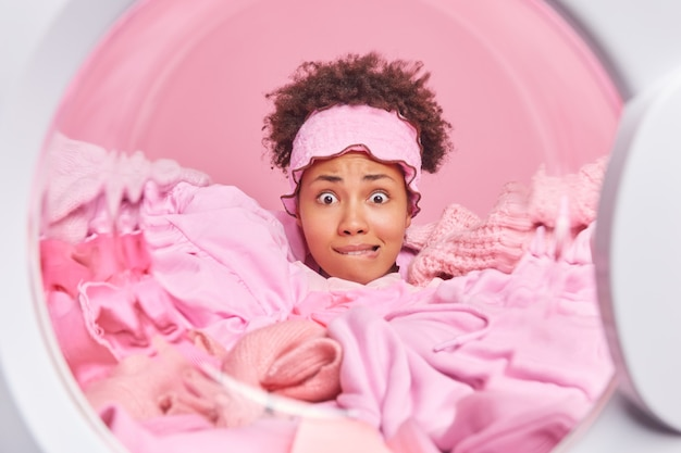 Widok z pralki nerwowej gospodyni domowej z kręconymi włosami ma wyraz niepokoju gryzie usta zatopione w stosie prania nosi opaskę zajętą pracami domowymi