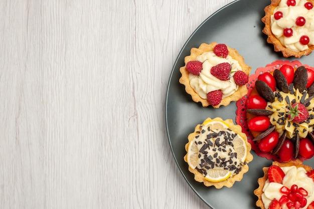 Widok z prawej strony na górze po prawej stronie ciasto czekoladowe zaokrąglone z tartami jagodowymi na szarym talerzu na białym drewnianym stole