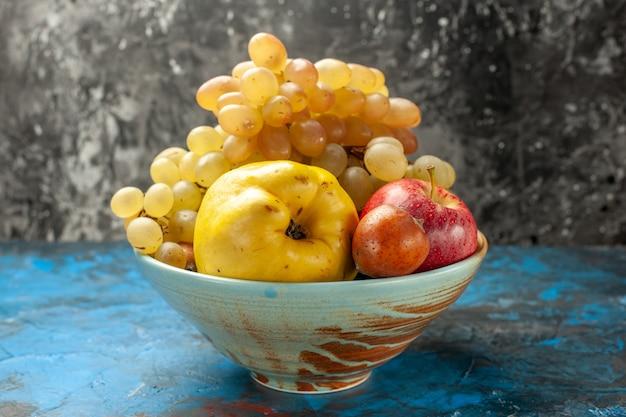 Widok z przodu aksamitne owoce pigwa jabłko i winogrona wewnątrz talerza na niebieskim tle zdrowie dieta witamina dojrzałe zdjęcie smaczne