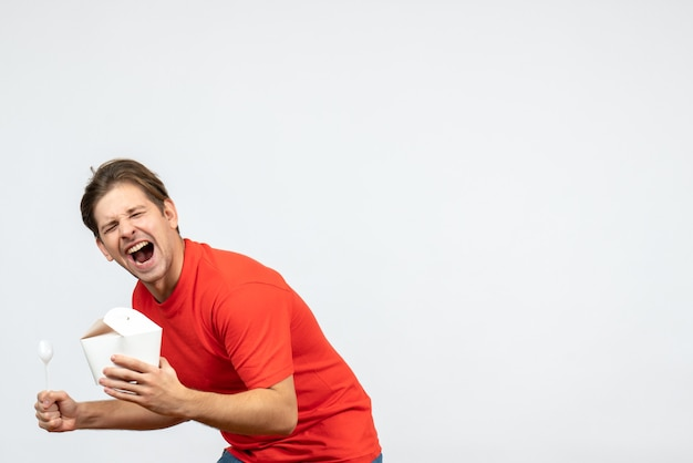 Widok z przodu ambitnego młodego faceta w czerwonej bluzce, trzymając papierowe pudełko i łyżkę na białym tle