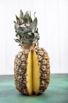 Widok z przodu ananasa z jednym kawałkiem wyciętym z całego owocu na powierzchni zielonej i białej