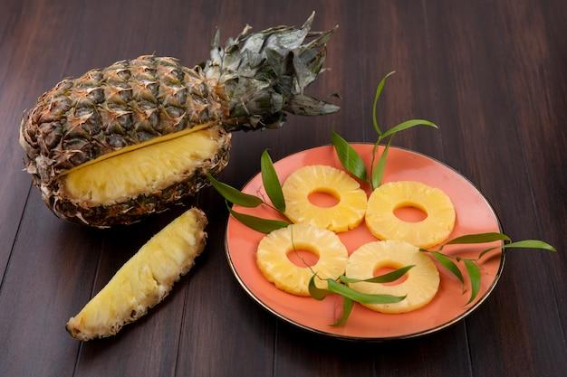 Widok z przodu ananasa z jednym kawałkiem wyciętym z całego owocu z plastrami ananasa w talerzu na drewnianej powierzchni