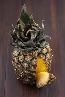 Widok z przodu ananasa z jednym kawałkiem wyciętym z całych owoców na drewnianej powierzchni