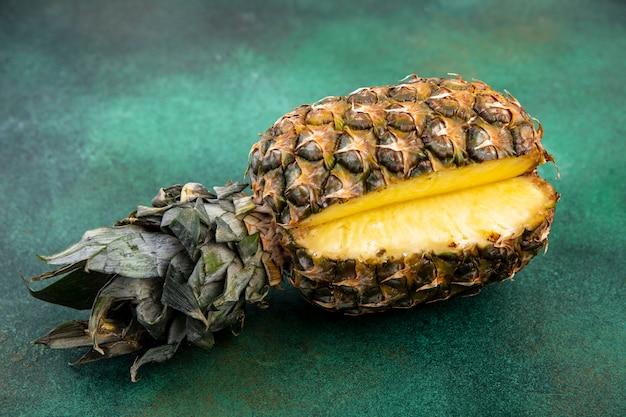 Widok z przodu ananasa z jednym kawałkiem wyciętym z całych owoców na zielonej powierzchni