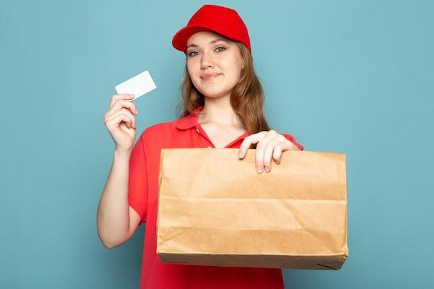 Widok z przodu atrakcyjna kobieta kurier w czerwonej koszulce polo czerwona czapka i dżinsy trzyma pakiet i białą kartę pozowanie uśmiechnięty na niebieskim tle praca gastronomiczna
