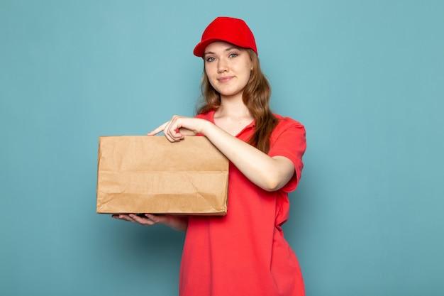 Widok z przodu atrakcyjna kobieta kurier w czerwonej koszulce polo czerwoną czapkę i dżinsy gospodarstwa pakiet pozowanie uśmiechnięty na niebieskim tle usługi gastronomiczne