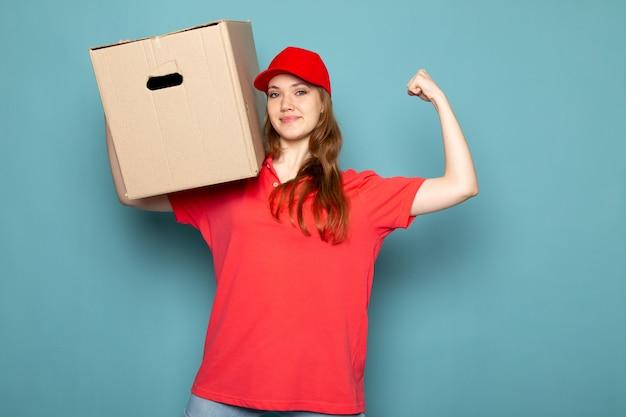 Widok z przodu atrakcyjna kobieta kurier w czerwonej koszulce polo, czerwonej czapce i dżinsach, trzymając pudełko, pozowanie, uśmiechając się, wyginając się na niebieskim tle