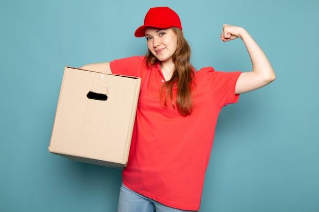 Widok z przodu atrakcyjna kobieta kurier w czerwonej koszulce polo czerwonej czapce i dżinsach zginając przytrzymanie pudełko pozowanie na niebieskim tle pracy gastronomicznej