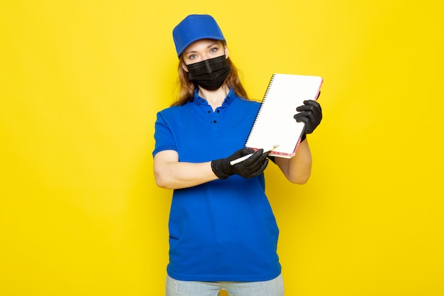 Widok z przodu atrakcyjna kobieta kurier w niebieskiej koszulce polo niebieska czapka i dżinsy w czarnych rękawiczkach czarna maska ochronna trzyma długopis i notatnik na żółtym tle praca gastronomiczna