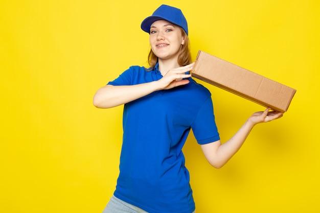 Widok z przodu atrakcyjna kobieta kurier w niebieskiej koszulce polo niebieskiej czapce i dżinsach, uśmiechając się, śpiesząc się, trzymając pakiet na żółtym tle usługi gastronomicznej