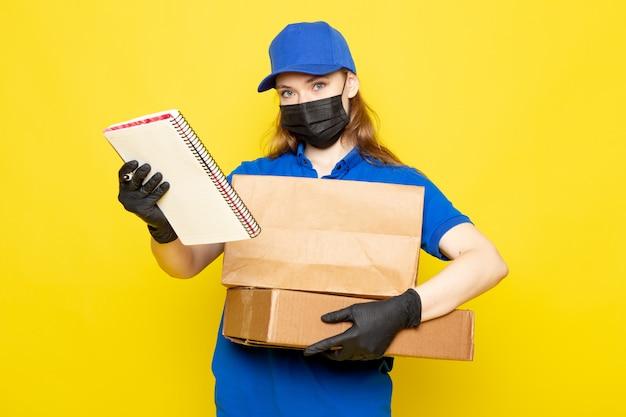 Widok z przodu atrakcyjna kobieta kurier w niebieskiej koszulce polo, niebieskiej czapce i dżinsach, z pakietem w czarnych rękawiczkach, czarna maska ochronna, stanowiąca na żółtym tle praca gastronomiczna