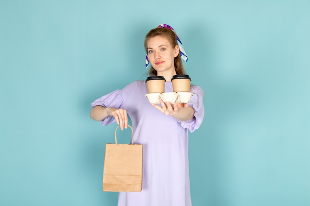Widok z przodu atrakcyjna kobieta w niebieskiej koszuli trzyma pakiet papieru i filiżanki kawy na niebiesko