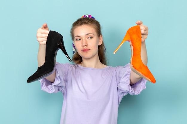 Widok z przodu atrakcyjna kobieta w niebieskiej koszuli trzymającej czarne i pomarańczowe buty na niebiesko