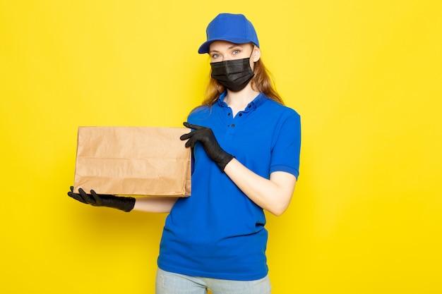 Widok z przodu atrakcyjna kurierka w niebieskiej koszulce polo, niebieskiej czapce i dżinsach, z pakietem w czarnych rękawiczkach, czarna maska ochronna na żółtym tle
