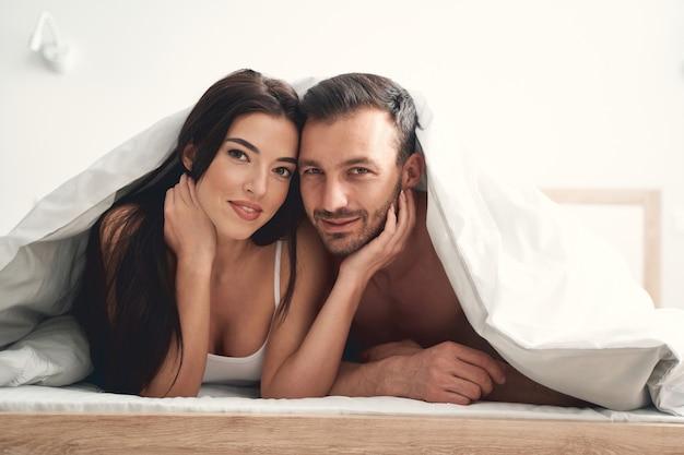 Widok z przodu atrakcyjnego mężczyzny i jego żony odpoczywających w łóżku pod kocem