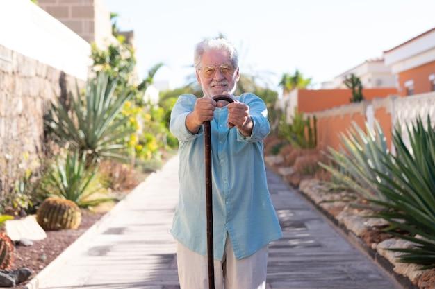 Widok z przodu atrakcyjnego uśmiechniętego starszego mężczyzny na zewnątrz, patrzącego na kamerę trzymającą laskę spacerową