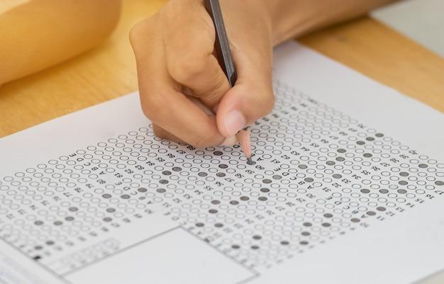 Widok z przodu azjatyckich studentów, licencjackich gospodarstwa ołówek pisania na wielu
