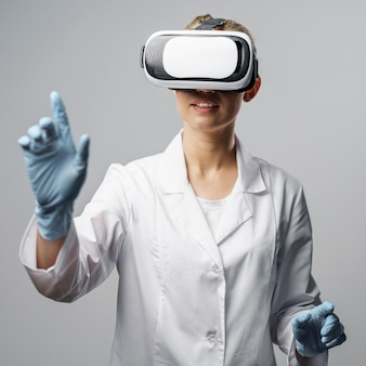 Widok z przodu badaczki korzystającej z zestawu słuchawkowego wirtualnej rzeczywistości