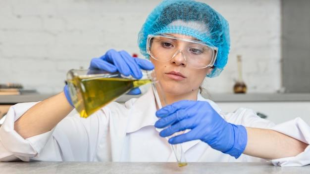 Widok z przodu badaczki z okularami ochronnymi i siatką na włosy podczas eksperymentów naukowych