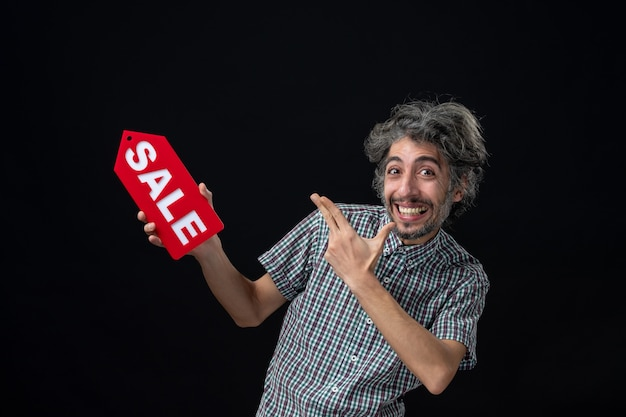 Widok z przodu bardzo podekscytowanego mężczyzny trzymającego czerwony znak sprzedaży na ciemnej ścianie