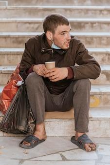 Widok z przodu bezdomnego na schodach, trzymając kubek i plastikową torbę
