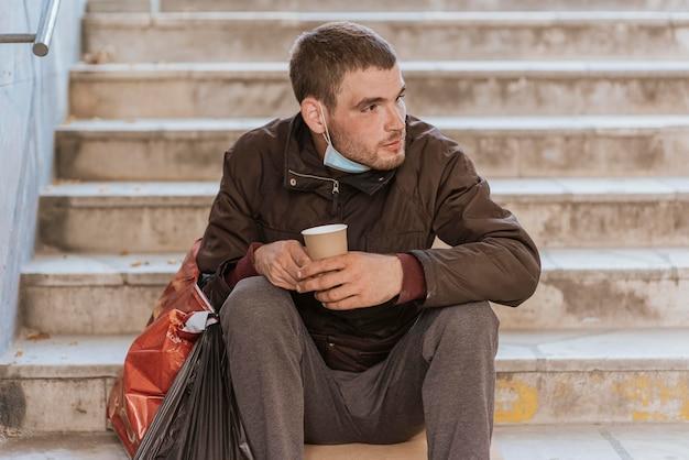 Widok z przodu bezdomnego trzymającego kubek i plastikową torbę na schodach