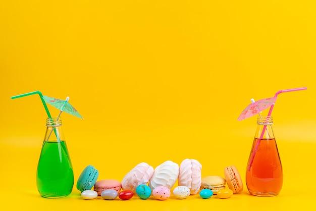 Widok z przodu bezy i macarons wraz z koktajlami na żółtych, ciastowych ciasteczkach cukierniczych