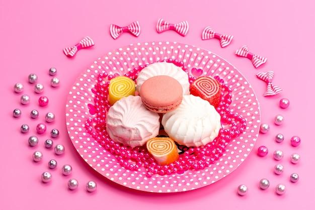 Widok z przodu bezy i makaroniki wewnątrz różu, talerz wraz z kokardkami na różowym, ciasto biszkoptowe