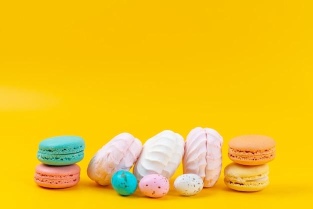 Widok z przodu bezy i makaroników pyszne i słodkie na żółtym, tęczowym kolorze