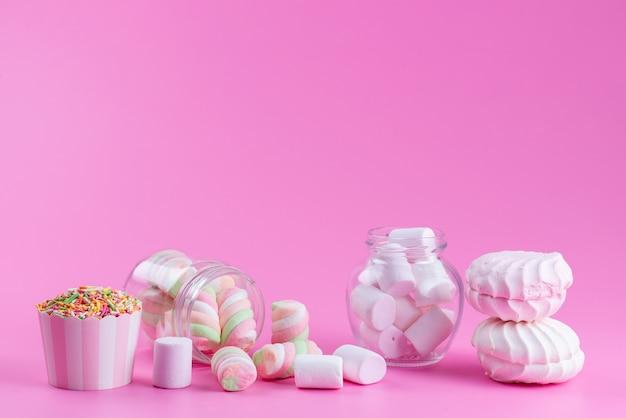 Widok z przodu bezy i pianek marshmallows słodkie i lepkie na różowym, kolorowym słodkim cieście biszkoptowym