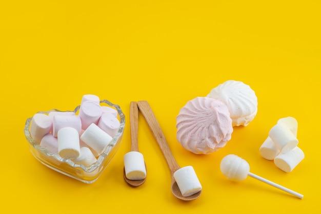 Widok z przodu bezy i pianek słodkich i pysznych na żółtym, cukrowo-cukierkowym kolorze