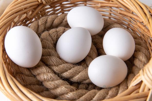 Widok z przodu białe całe jajka w koszyku na białym biurku.