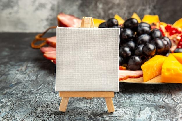 Widok z przodu białe płótno na drewnianych sztalugowych plasterkach mięsa winogron na drewnianej płycie na ciemnym