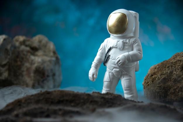 Widok z przodu białego astronauty ze skałami na księżycowym niebieskim biurku pogrzeb śmierci science fiction