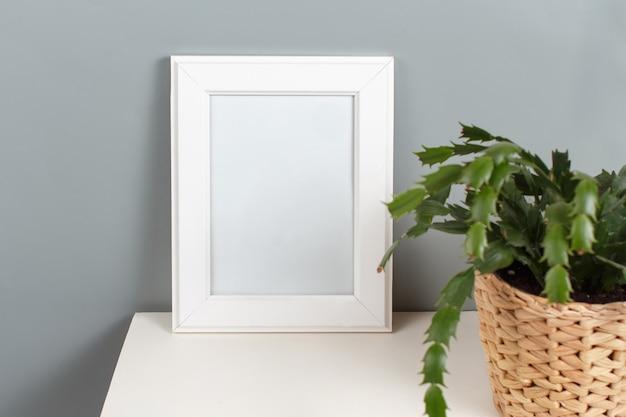 Widok z przodu białej ramki plakatowej z rośliną w doniczce na szarej ścianie