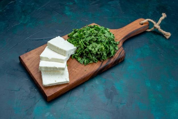 Widok z przodu biały ser ze świeżymi zieleniami na ciemnoniebieskim tle.