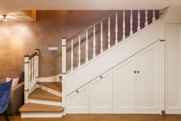 Widok z przodu białych schodów na drugie piętro z wbudowanymi szafkami wykonanymi z drewna. klasyczne wnętrze pokoju gościnnego w dwupoziomowym mieszkaniu.