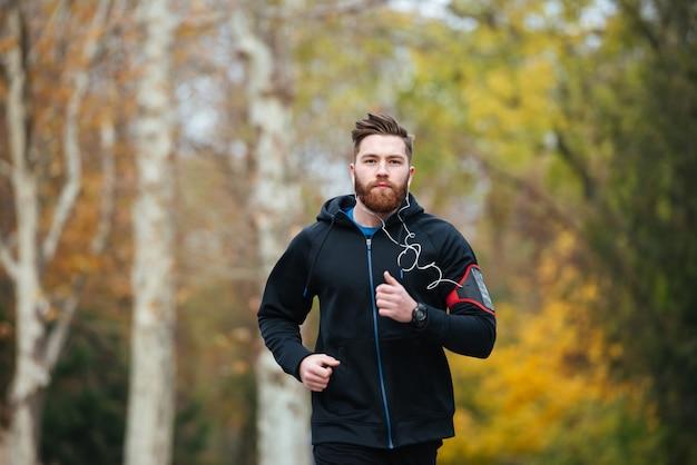 Widok z przodu biegacza w parku patrzącego na kamerę