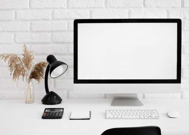 Widok z przodu biurka z komputerem i lampą