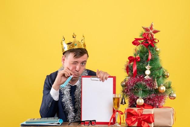 Widok z przodu biznesmen miga na aparat siedzący przy stole w pobliżu choinki i przedstawia na żółtej ścianie